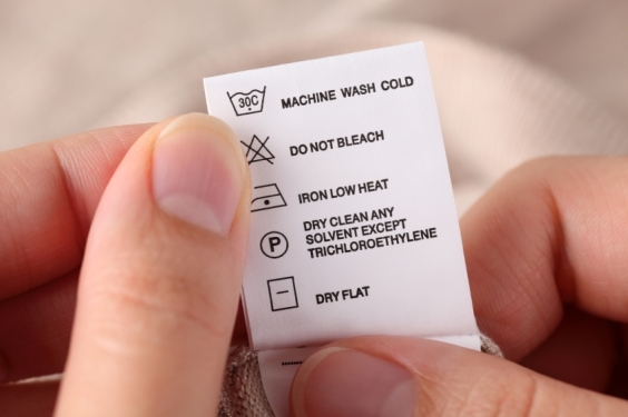 Woman's hands holding clothes label with cleaning instructions.